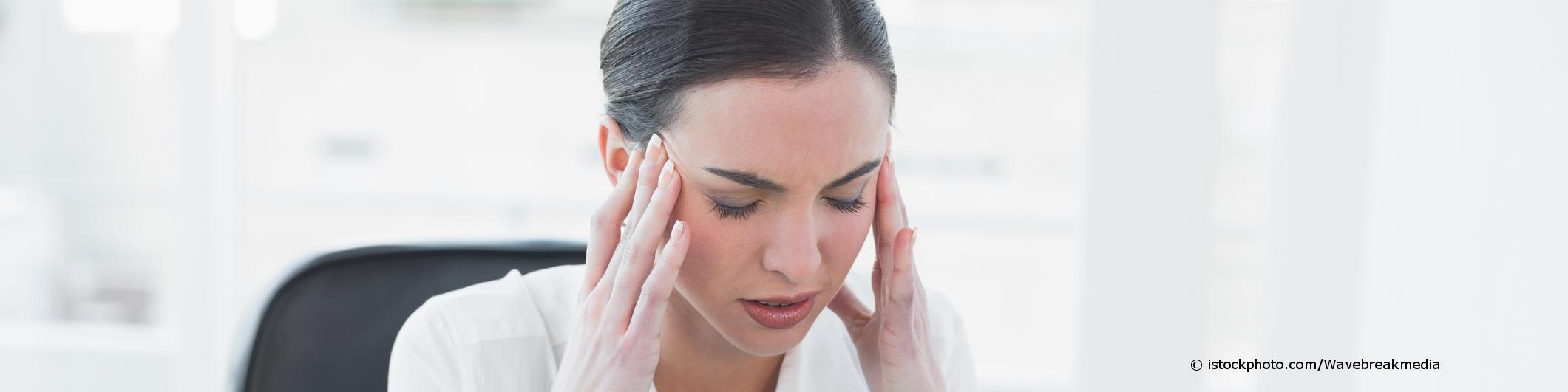 Junge Frau mit Kopfschmerzen sitzt am Schreibtisch und hält sich die Schläfen