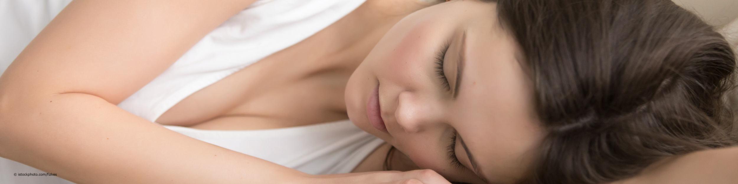 Junge Frau hat bei DocInsider die Tipps gegen Schlafstörungen gelsen und liegt nun entspannt auf der Seite im Bett.