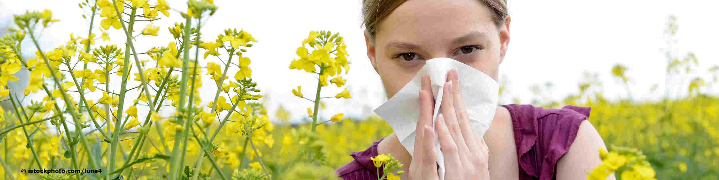 Mädchen im Rapsfeld leidet wegen Heuschnupfen unter tränenden Augen und laufender Nase.