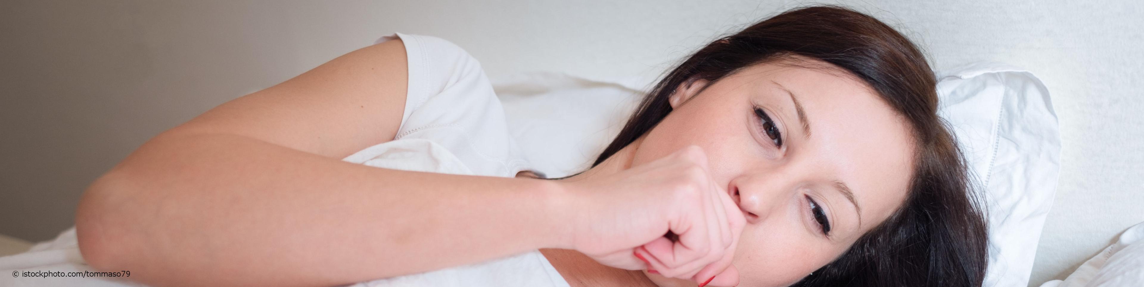 Frau mit Bronchitis liegt mit Fieber im Bett und hat einen Hustenanfall.