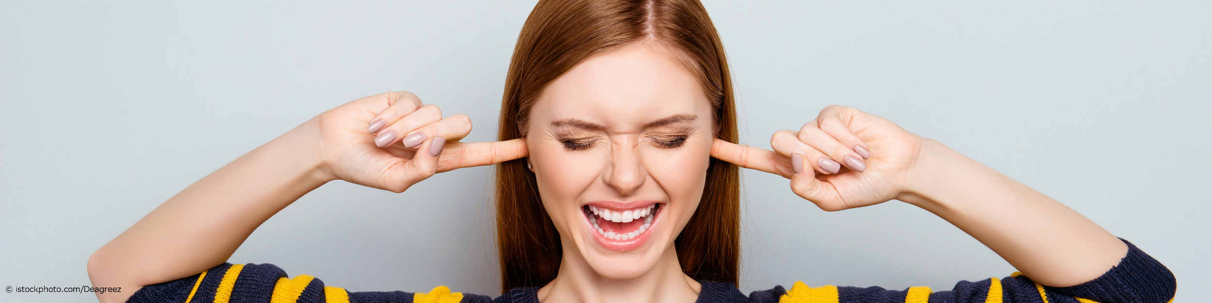Frau mit Tinnitus hält sich die Ohren zu, weil sie von den ständigen Geräuschen in ihren Ohren genervt ist.
