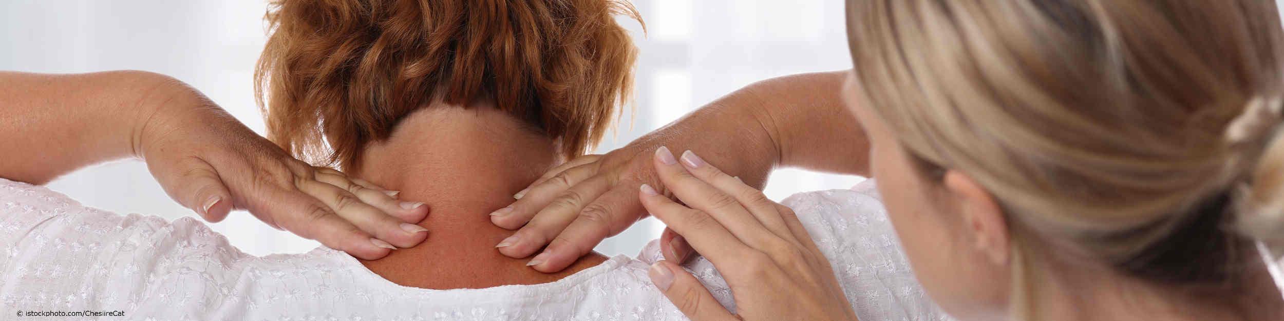 Fachärztin für Arbeitsmedizin untersucht Angestellte mit Nackenschmerzen.
