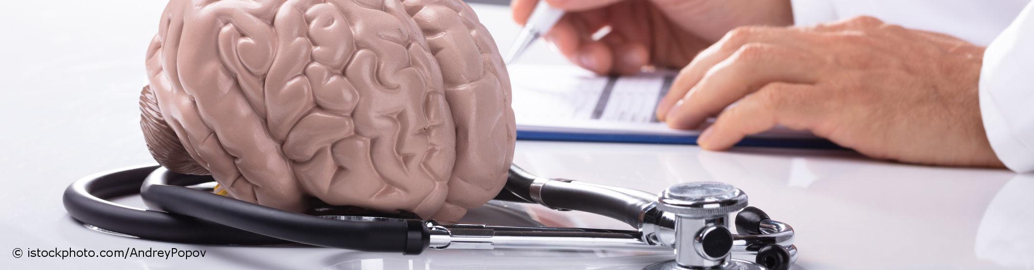 Auf docinsider registrierter Neurologe sitzt vor einem Modell des menschlichen Gehirns, um das ein Stethoskop gewickelt ist.