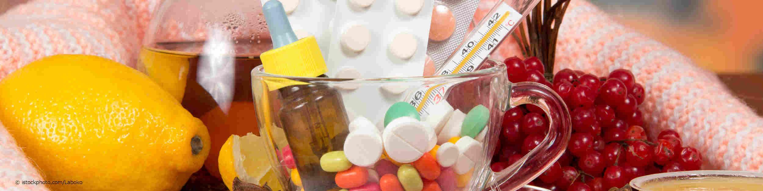 Eine Teetasse voller Tabletten sowie einem Tinkturfläschchen inmitten von Zitrone, Himbeeren und Johannisbeeren - zusammen eingenommen könnte es Probleme geben.