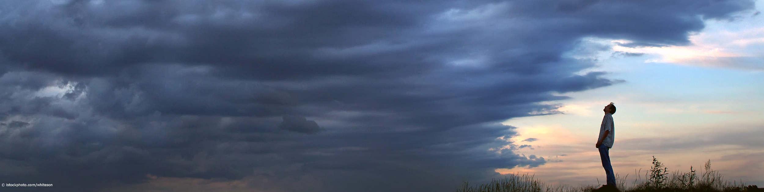 Resilienter Mann steht im Licht und schaut auf eine dunkle Wolkenwand.
