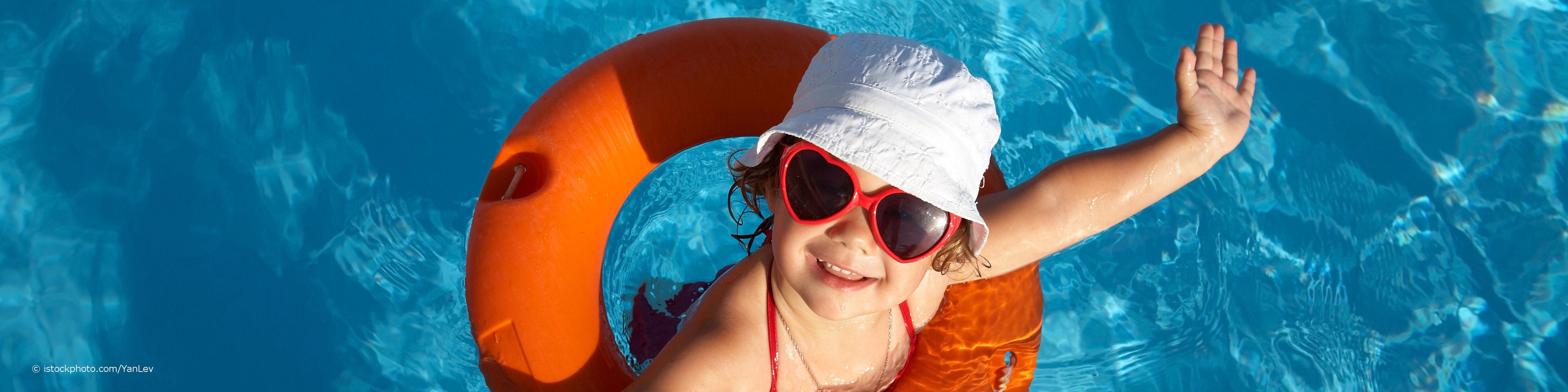 Kind trägt eine Sonnenbrille mit UV-Schutz, einen Hut und einen Schwimmreifen und winkt aus dem Wasser im Schwimmbad