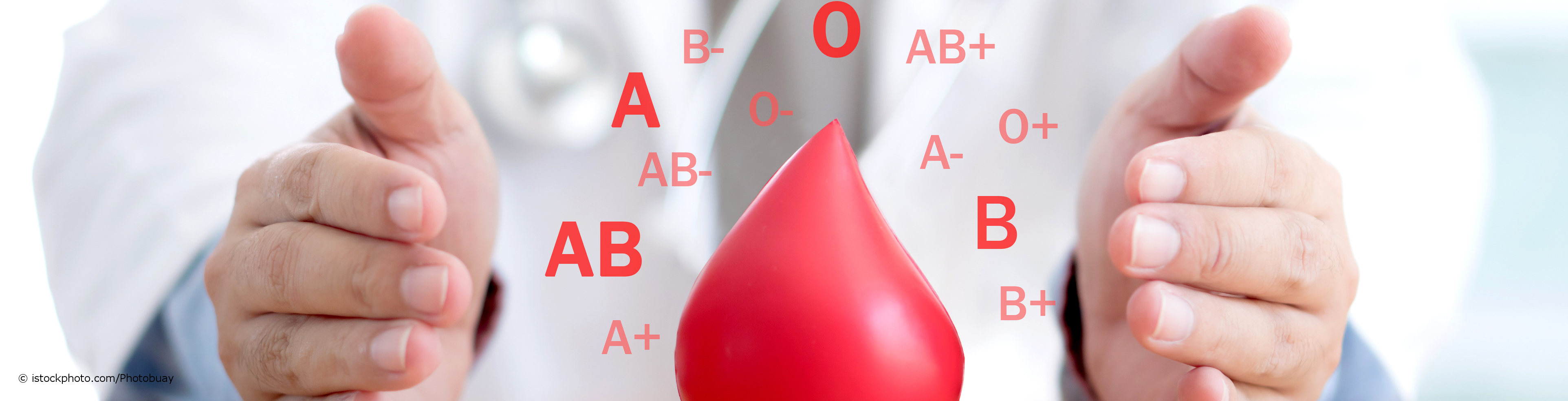 Transfusionsmediziner umschließt mit seinen Händen ein Modell eines Blutstropfens, der von Blutgruppen (A, B, AB, 0 und Rhesusfaktoren (+-) umgeben ist.