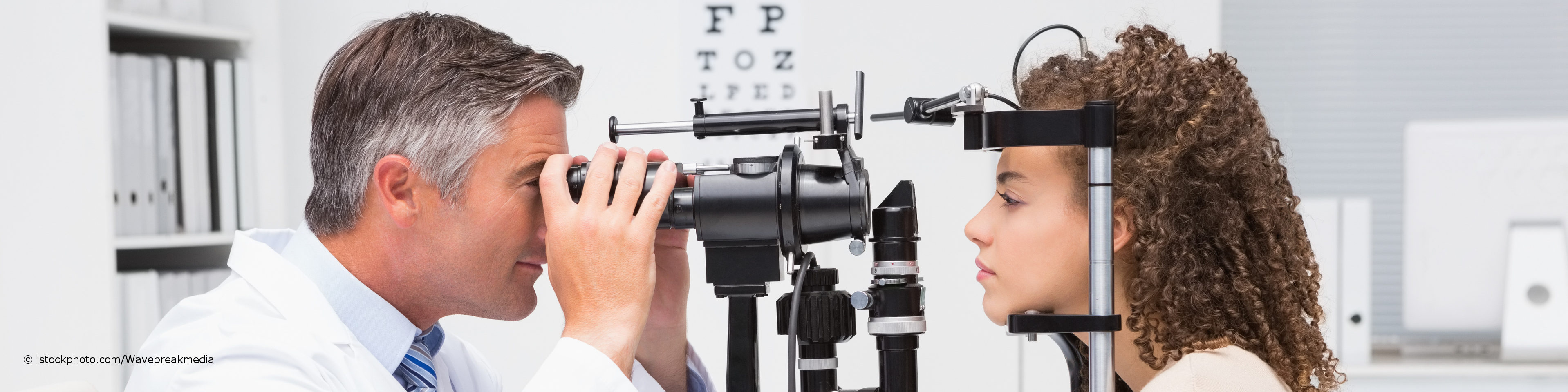 Ein Augenarzt untersucht die Augen einer Patientin an der Spaltlampe auf Erkrankungen, Sehschwächen und Fehlsichtigkeiten