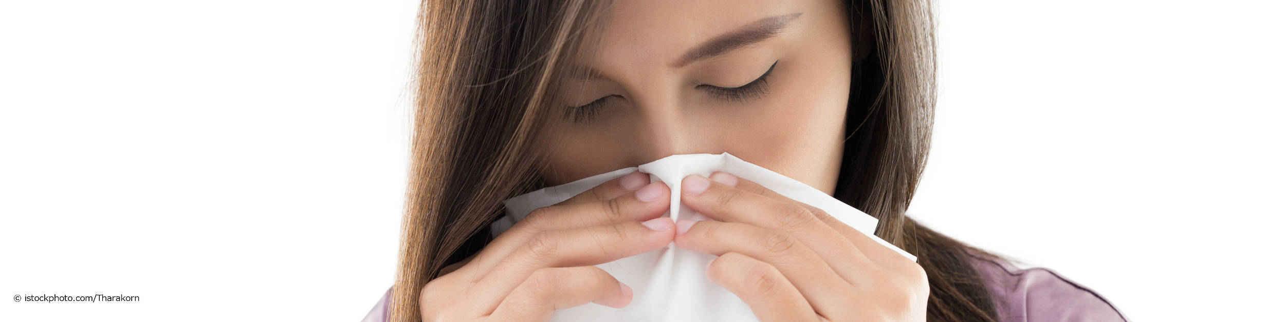 Junge Frau hat die Tipps gegen Nasenbluten von DocInsider gelesen und beugt ihren Kopf nach vorne und drückt sich ein Taschentuch gegen die Nasenflügel