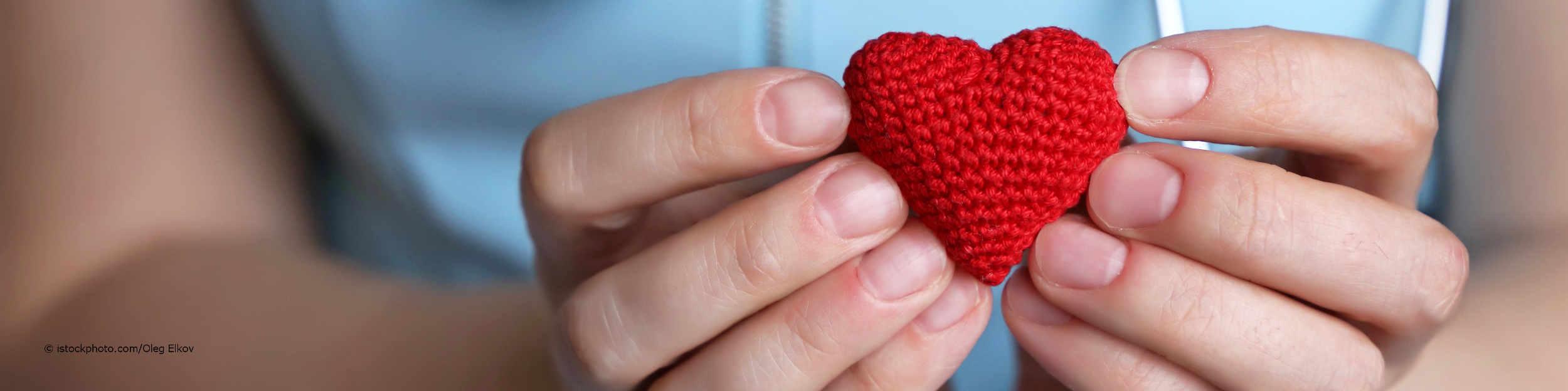 Kardiologin hält als Symbol für eine Herzklappenspende ein Herz aus Stoff in den Händen