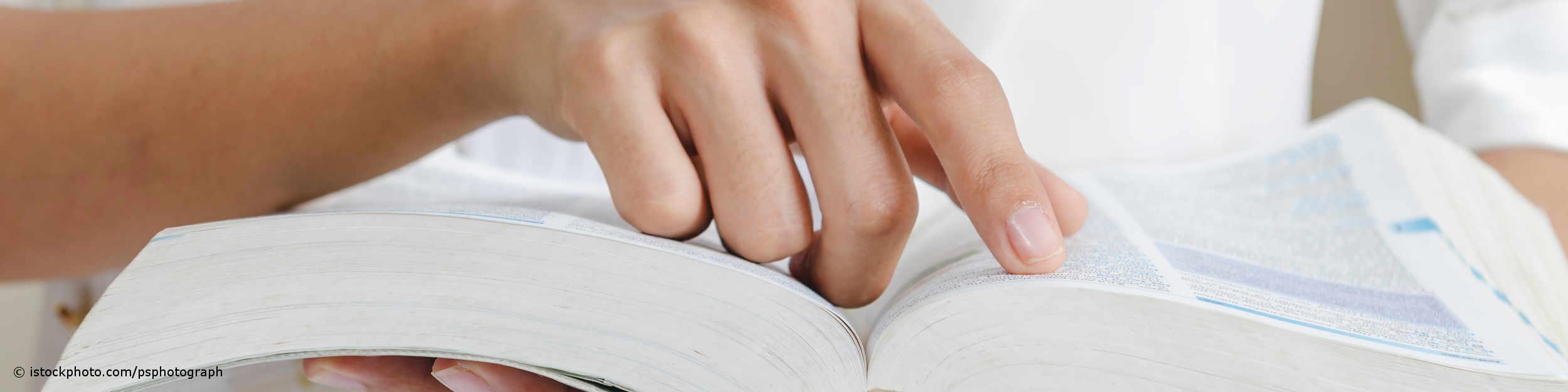 Finger fährt auf der Suche nach den Begriffen im Corona-ABC von DocInsider über ein aufgeschlagenes Lexikon