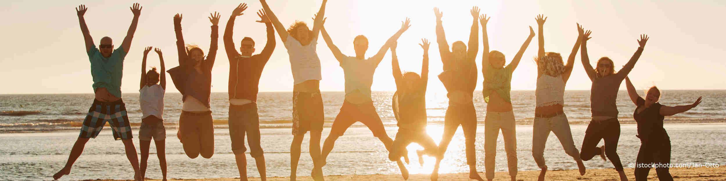 Junge Leute haben auf DocInsider die Tipps zur Stärkung des Immunsystems gelesen und hüpfen im Sonnenuntergang auf dem Sand am Meer.