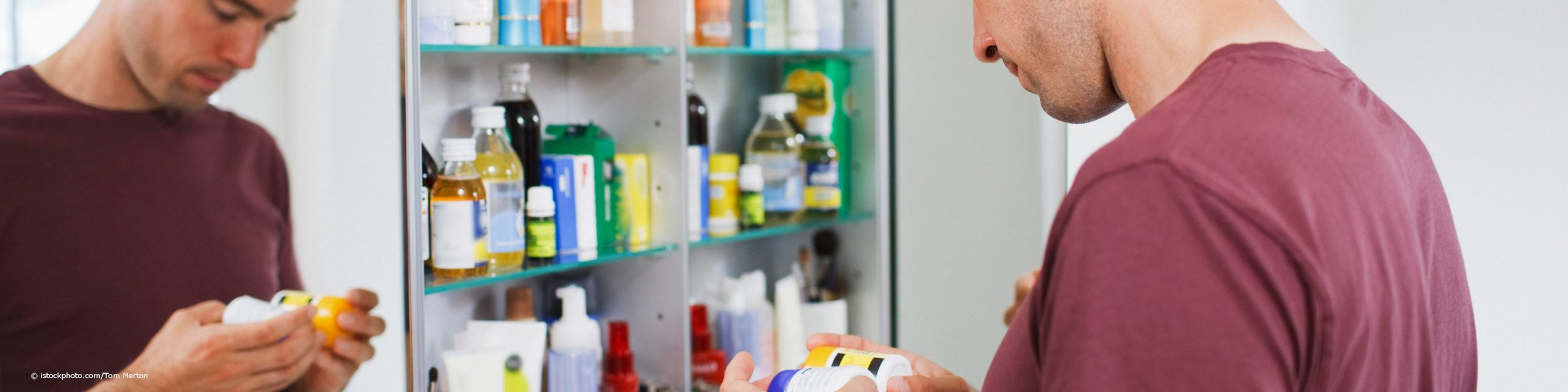 Mann kontrolliert seinen Medizinschrank.