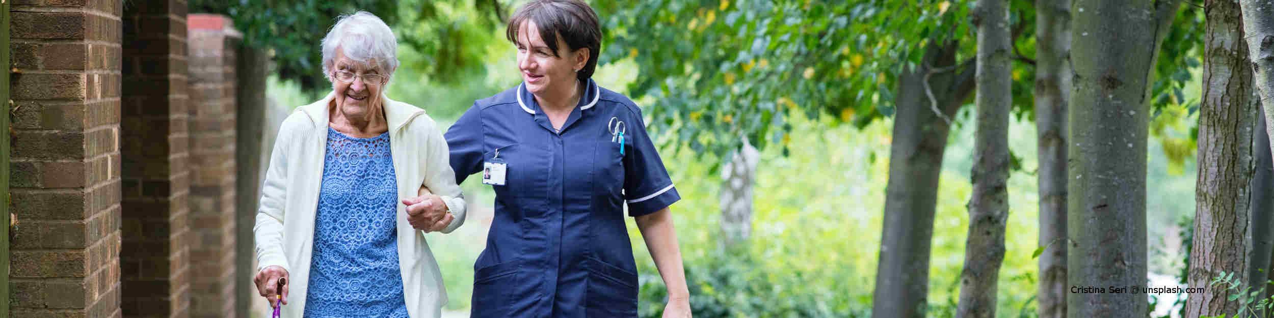 Pflegebedürftige Seniorin geht mit ihrer 24-Stunden-Pflegekraft im Park spazieren