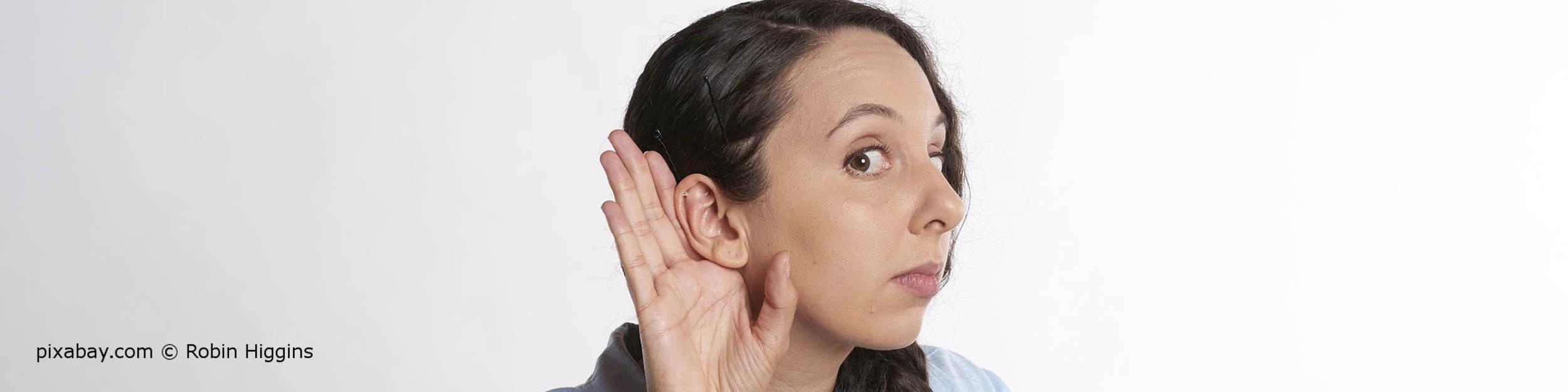 Junge Frau mit Schmalzpfropf im Ohr hört nicht mehr richtig.